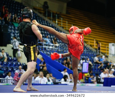 JAKARTA, INDONESIA - NOVEMBER 15, 2015: Ishan Naligamage of Sri Lanka (red) fights Saipiev Ilgizbek of Kazakhstan (black) in the men's 70kg Sanda event at the 13th World Wushu Championship 2015.