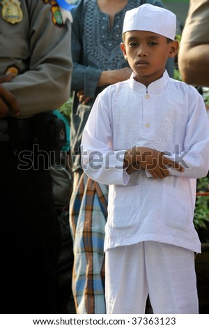 JAKARTA, INDONESIA - SEPTEMBER 20: A young Muslim boy stands and prays outside a mosque in Jakarta on Hari Raya, the end of a month of fasting called Ramadan September 20, 2009 in Jakarta.