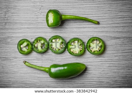 Jalapeno pepper on gray wooden surface. - stock photo