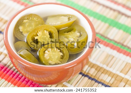 Jalapenos - Pickled sliced jalapeno chillies in a bowl on a colourful background.