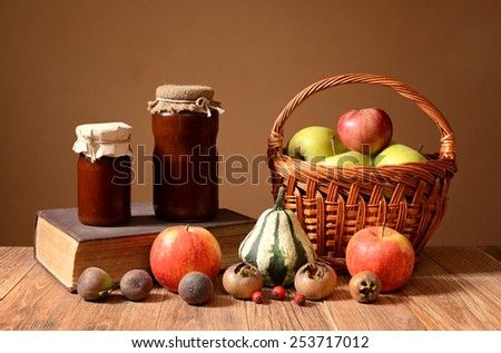 Jam into jars, books, and fruits in wicker basket on the table - stock photo