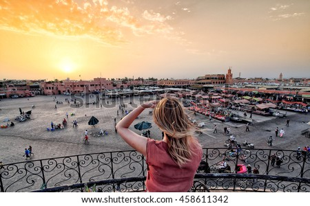 Jamaa el-Fna market Marrakech at sunset. Tourist watching the shops in the old medina.   - stock photo