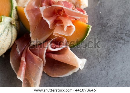 Jambon mix. Ham. Traditional Italian and Spanish salting, smoking, dry-cured dish - jamon Serrano and prosciutto crudo sliced with melon on grey background. Copy space. Closeup. - stock photo
