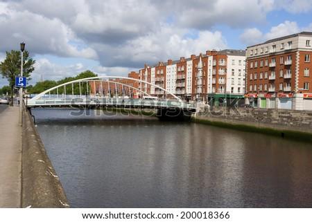 James Joyce Bridge over river Liffey and row houses in the city of Dublin in Ireland. - stock photo