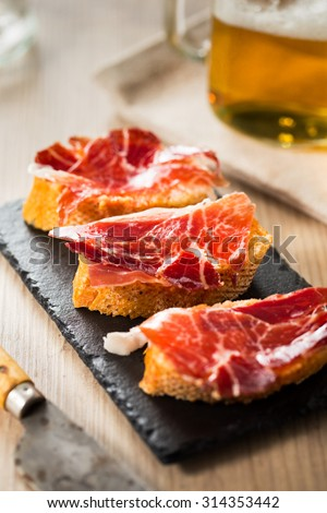 Jamon iberico, the best spanish ham tapas on a slice of bread and beer. - stock photo