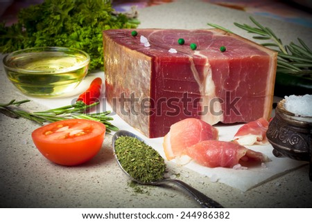 Jamon with herbs and spices, salt, olive oil and tomatoes on stone background. Toned. - stock photo