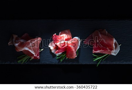 jamon with rosemary on a black background - stock photo