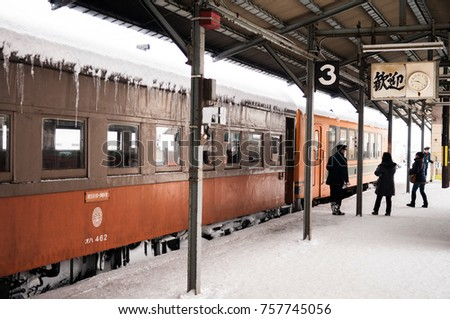 JAN 21, 2014 Aomori, Japan : Train conductor waiting passenger to board on classic old potbelly stove train opperated on Tsugaru railway in winter snow at Goshogawara station, Aomori, Tohoku, Japan.