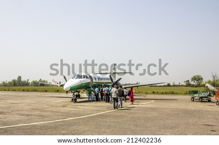 JANAKPUR, NEPAL - MARCH 20, 2014: A small airplane flying from Janakpur to Kathmandu. People are just starting to board the plane.