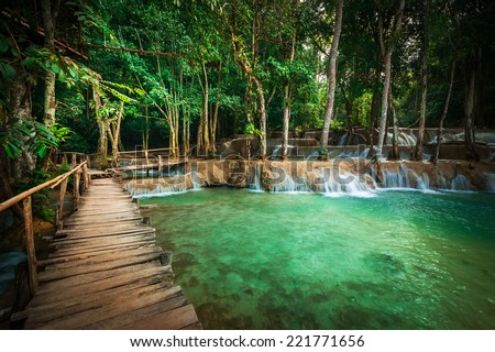 Jangle landscape tropical rain forest landscape with wooden bridge with amazing turquoise water of Kuang Si cascade waterfall at tropical rain forest near Luang Prabang, Laos - stock photo