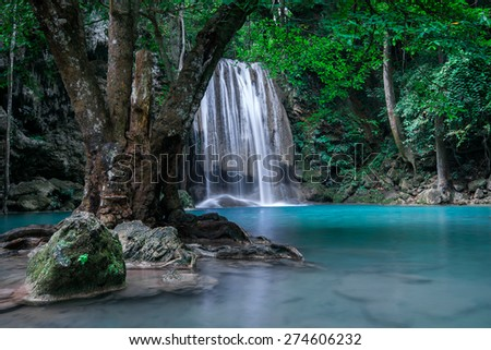 Jangle landscape with flowing turquoise water of Erawan cascade waterfall at deep tropical rain forest. National Park Kanchanaburi, Thailand - stock photo