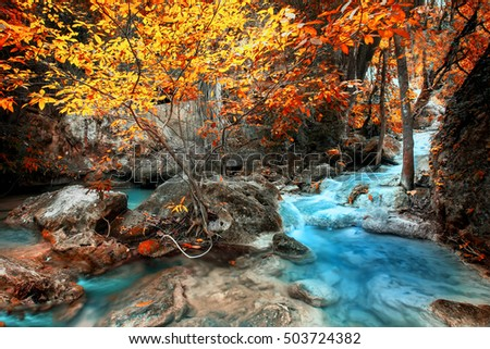 Jangle landscape with flowing turquoise water of Erawan waterfall at deep tropical rain forest. National Park Kanchanaburi, Thailand