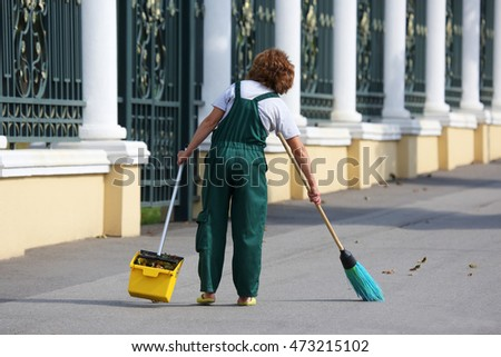 janitor cleans the sidewalk of the city from fallen leaves