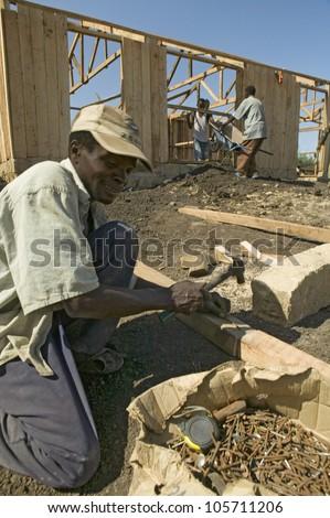 JANUARY 2007 - Man helps construct new houses for Pepo La Tumaini Jangwani, HIV/AIDS Community Rehabilitation Program, Orphanage & Clinic. Nairobi, Kenya, Africa - stock photo