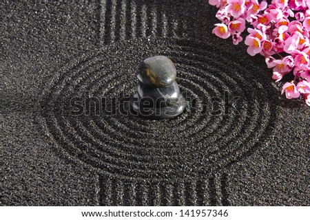 Japan garden with stacked stones in raked sand - stock photo