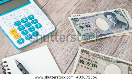 Japan money - Japanese yen currency and Calculator, notebook, pencil on wooden background  - stock photo
