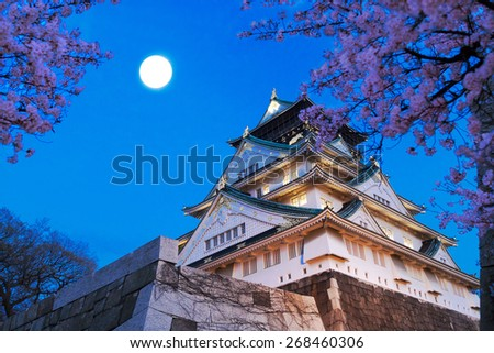Japan. Osaka castle with cherry blossom. Night view with full moon. - stock photo