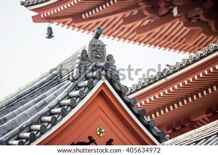 Japanese art at roof of Sensoji temple, Asakusa, Tokyo in Japan, under blue sky - stock photo