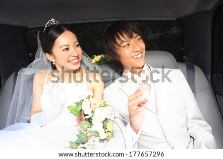 Japanese Bride and groom waving hands inside of the car - stock photo