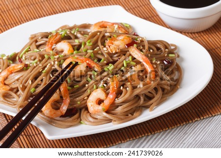 Japanese buckwheat soba noodles with shrimp and sesame seeds on a plate close-up. horizontal  - stock photo