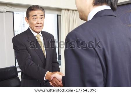 Japanese Businessman shaking hands - stock photo