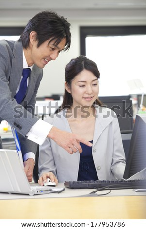 Japanese businesswoman and businessman looking at the personal computer