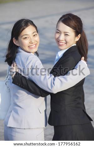 Japanese businesswoman turning around while snuggle - stock photo