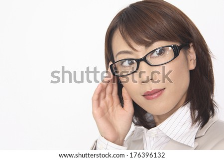 Japanese businesswoman with one hand raising up the edge of glasses