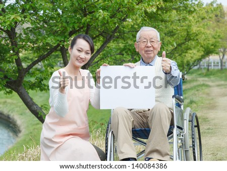 Japanese caregivers and senior with thumb up in the field