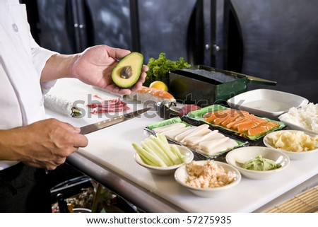 Japanese chef in restaurant with fresh ingredients for making sushi rolls - stock photo
