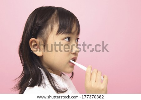 Japanese child brushing her teeth