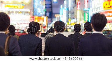 Japanese corporative business people in suits, waiting in rush hour on crossroad in Shinjuku business district, Tokyo, Japan. Blured advertising boards illuminated in the background. - stock photo