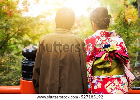 Japanese couple with Traditional Yukata and Kimono enjoy autumn foliage color at sunset, Kyoto, Japan