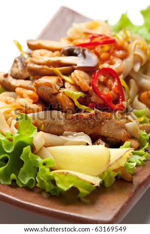 Japanese Cuisine - Fried Noodles with Pork and Seadood and Vegetables. Garnished on Salad Leaf