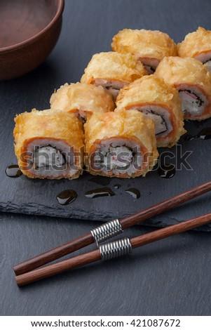 Japanese cuisine. Roll sushi set on a black slate board - stock photo