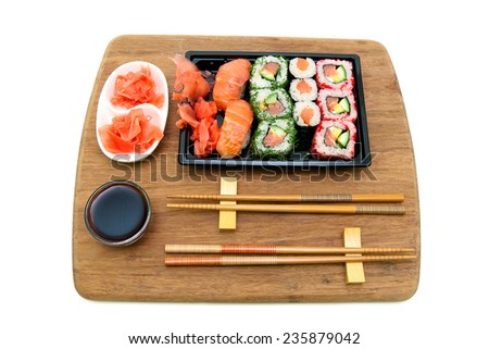 Japanese cuisine: rolls and sushi on a bamboo board isolated on white background. horizontal photo.