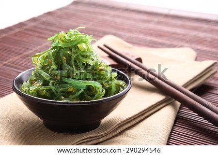 Japanese Cuisine, Seaweed Salad in black bowl on bamboo mat. - stock photo