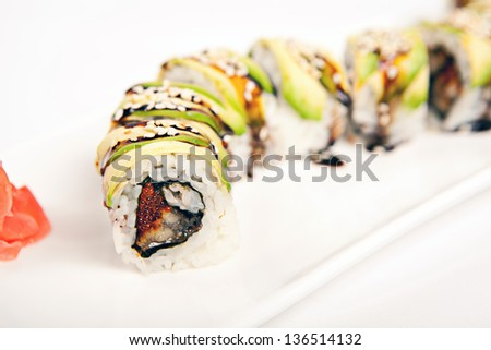 Japanese Cuisine - Sushi Roll with Cucumber, Cream Cheese and Smoked Eel inside. Topped with Shrimp. Garnished with Unagi Sauce - stock photo