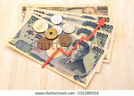 Japanese currency and red up arrow - stock photo