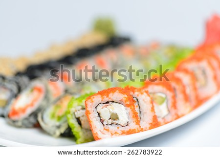 Japanese dish of different sushi rolls on light background - stock photo
