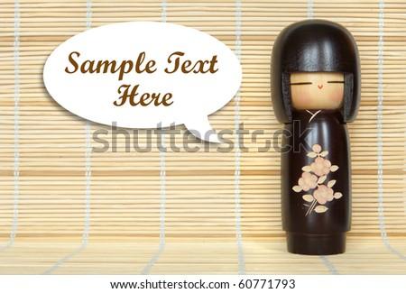 japanese doll on bamboo mat background - stock photo