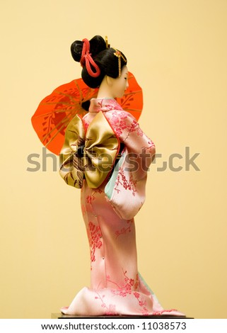 Japanese doll posing with neutral background - stock photo