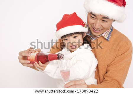 Japanese Father and daughter pour champagne into a glass at Christmas time