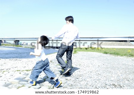 Japanese father and son walking along a river