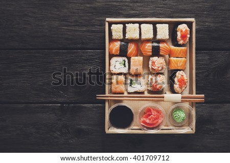 Japanese food restaurant, catering, maki gunkan roll plate or platter. Sushi with chopsticks, ginger, soy sauce, wasabi at rustic wood background in take away, set delivery box. Top view.  - stock photo