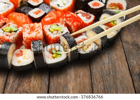 Japanese food restaurant delivery - sushi maki california roll platter set isolated at wooden background closeup with wooden chopsticks taking one piece - stock photo