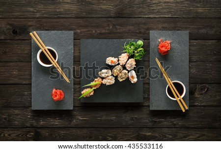 Japanese food restaurant, salmon sushi maki gunkan roll plate or platter set. Chopsticks, ginger, soy, wasabi. Sushi at black stone mat and rustic wood background. Top view, flat lay, copy space - stock photo