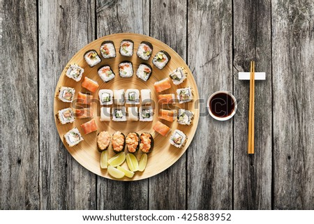 Japanese food restaurant, sushi maki gunkan roll plate or platter set. Chopsticks, ginger and wasabi. Sushi at bamboo round plate, rustic wood background. Top view with soy sauce - stock photo