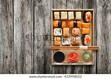Japanese food restaurant, sushi maki gunkan roll plate or platter set. Chopsticks, ginger, soy sauce, wasabi. Sushi on rustic wood background, take away, delivery box. Top view. - stock photo