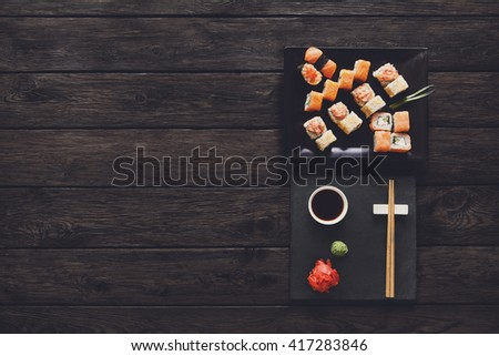 Japanese food restaurant, sushi maki gunkan roll plate or platter set. Free, copy space, chopsticks, ginger and wasabi. Sushi at rustic wood background and black stone. Top view at black. Flat lay. - stock photo